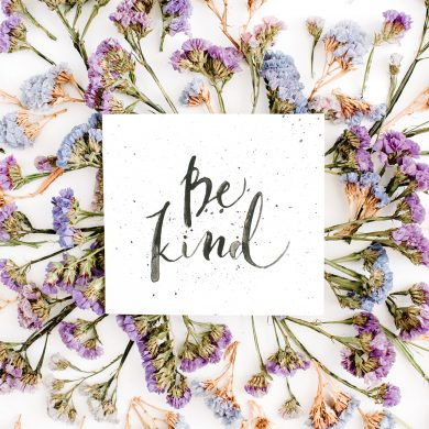 """Words """"Be Kind"""" written in calligraphic style on paper with blue and purple dried flowers on white background. Flat lay, top view"""